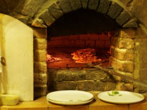 A picture of a brick pizza oven with a open fire.