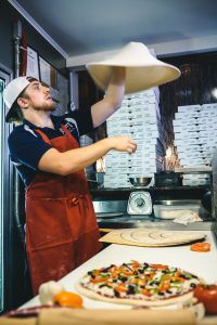 A pizzaioli making a pizza with pizza tools like a pizza oven