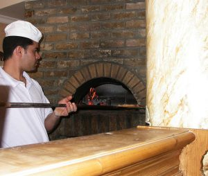 A pizza man using a traditional brick pizza oven and using a long handle pizza peel